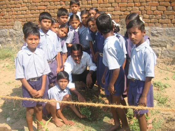 Students helping the birthday boy plant the tree