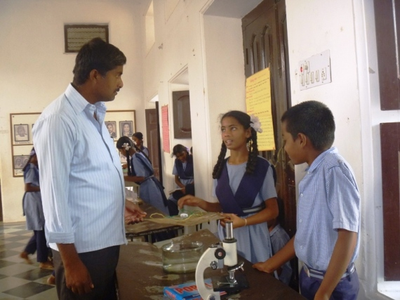 A parent interacts with High School students in the Science Exhibition