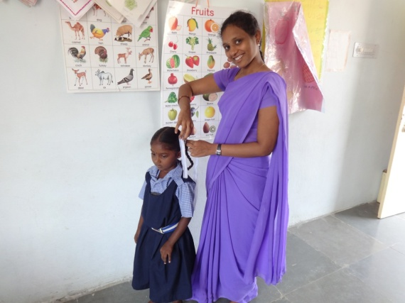 Mounika Teacher helping a student with hair grooming