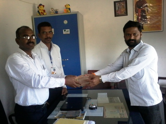 Mr. Suresh making the cash donation to Rollakal School Headmaster