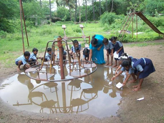 Children plying rain water with boats.1
