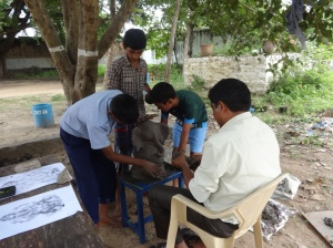 A teacher & students preparing the clay Ganesha together