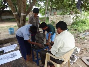 A teacher & students preparing the clay Ganesha together