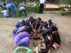 A teacher & young girls preparing the Boddemma idol together